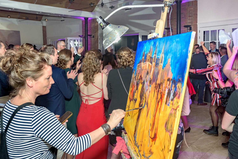 het bruidspaar verschijnt op het doek | Live Paint op trouwfeest voor de volkskrant | sas schilten fotografie